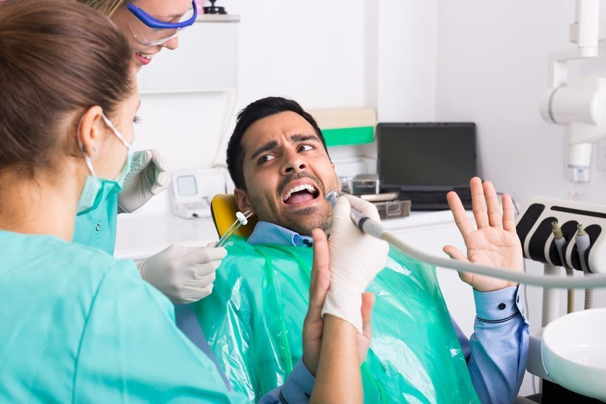 Dentist with assistant and scared male patient during check up at dental clinic